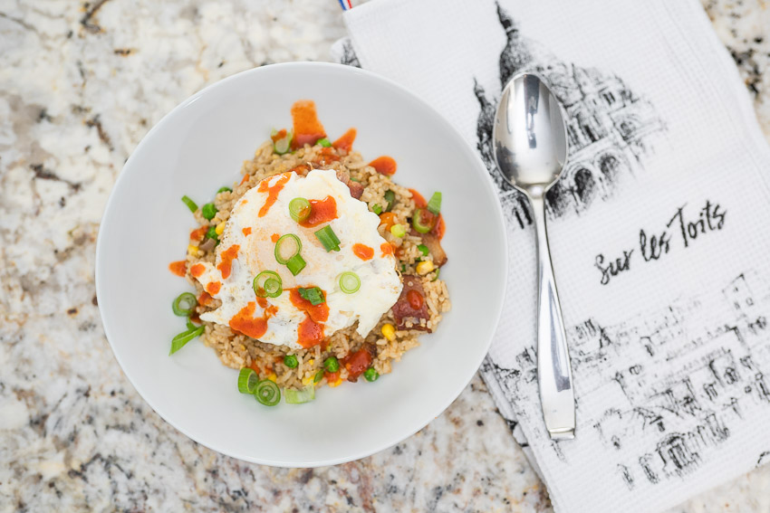Bacon Fried Rice with a fried egg top drizzled with Sriracha sauce