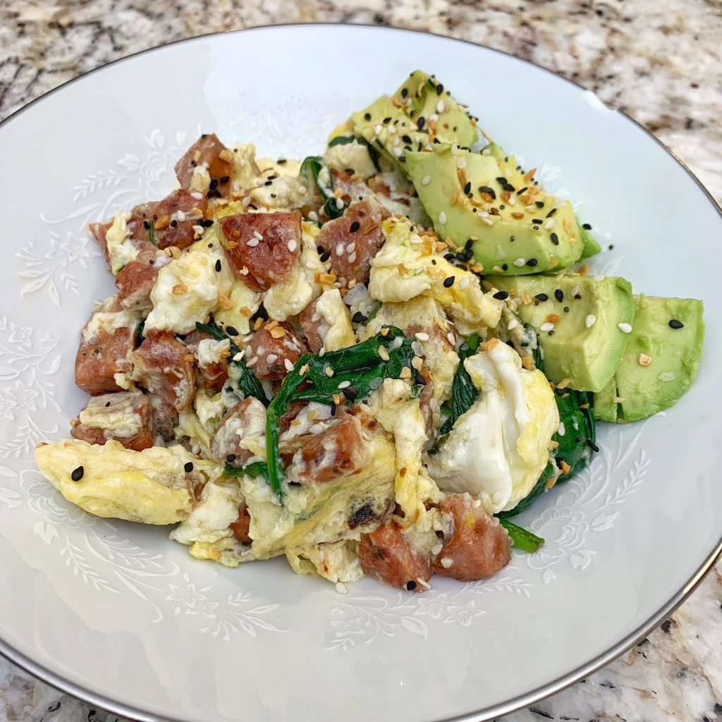 Egg, sausage, spinach scramble with avocado and Trader Joes Bagel Seasoning on a white plate.