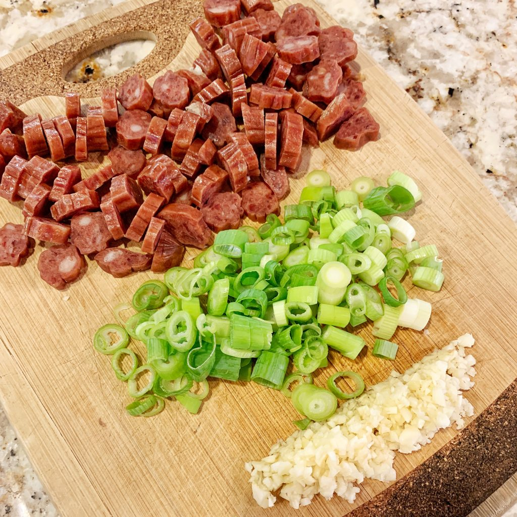 Minced garlic, diced scallions and Chinese sausage on a cutting board
