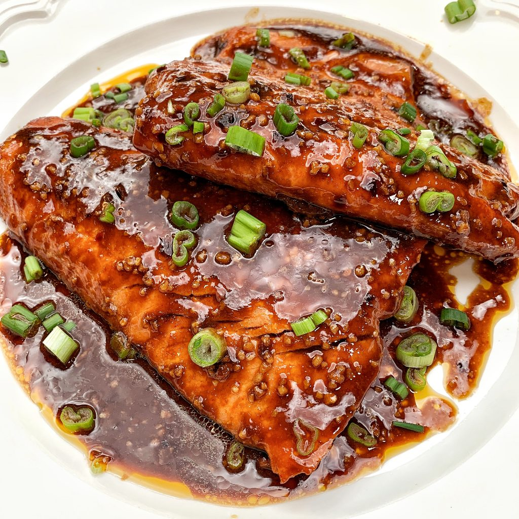 salmon on a white plate with sauce and garnished with green onions